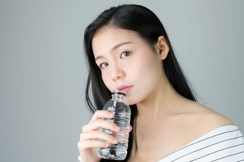 Mulher asiática com pele perfeita (benefícios do colágeno hidrolisado) bebendo água