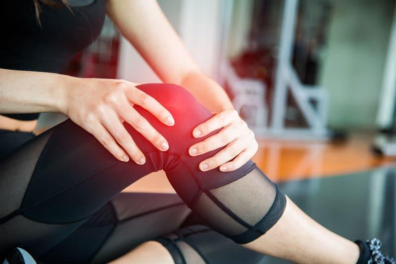 mulher com roupa de exercício com dor no joelho, benefícios do colágeno hidrolisado