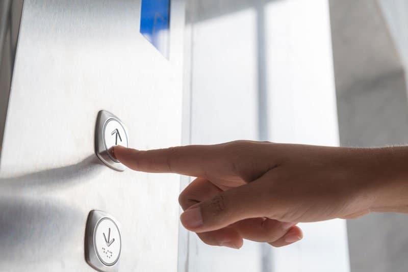 dedo apertando o botão do elevador para subir com lifesolic