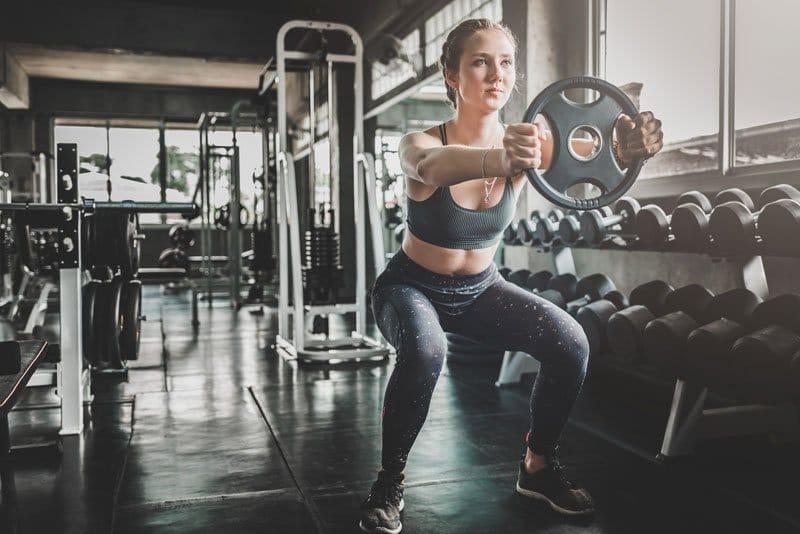 mulher com peso dentro da academia
