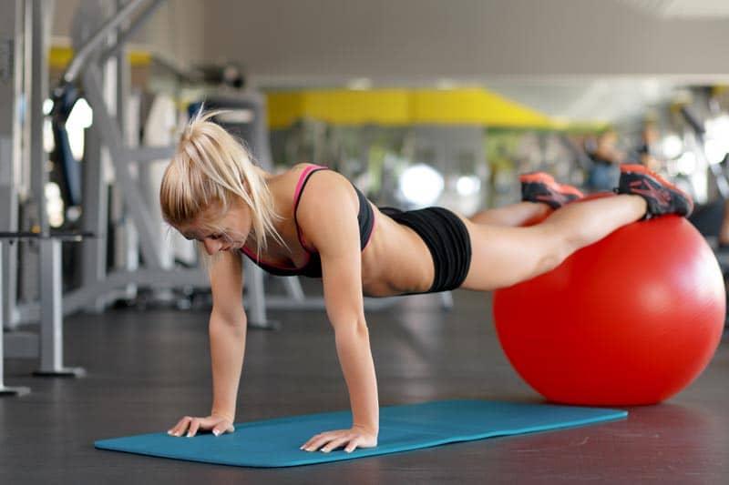 mulher fazendo flexão nos braços para aumentar hipertrofia feminina