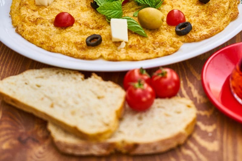 pão integral, tomates e um prato com comida mediterrânea
