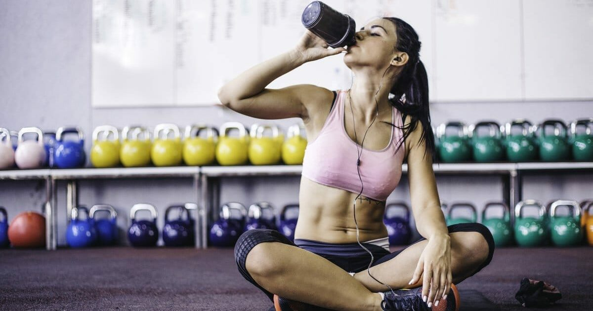 mulher sentada na academia bebendo algo numa coqueteleira de shake