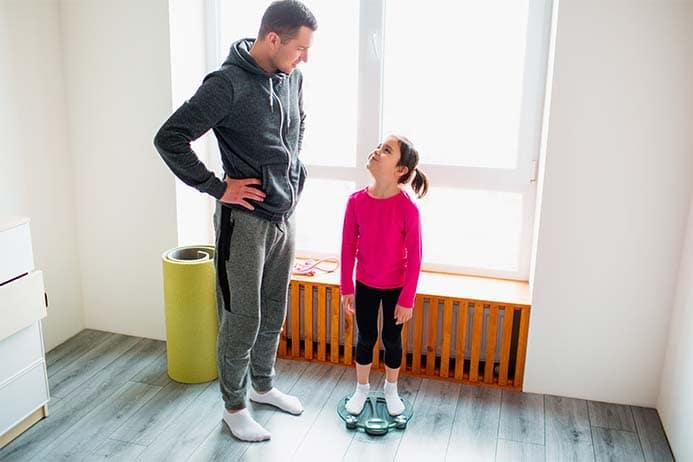 Homen inspirando criança a fazer exercícios