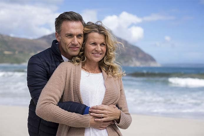 Casal de meia idade abraçados contemplando o mar