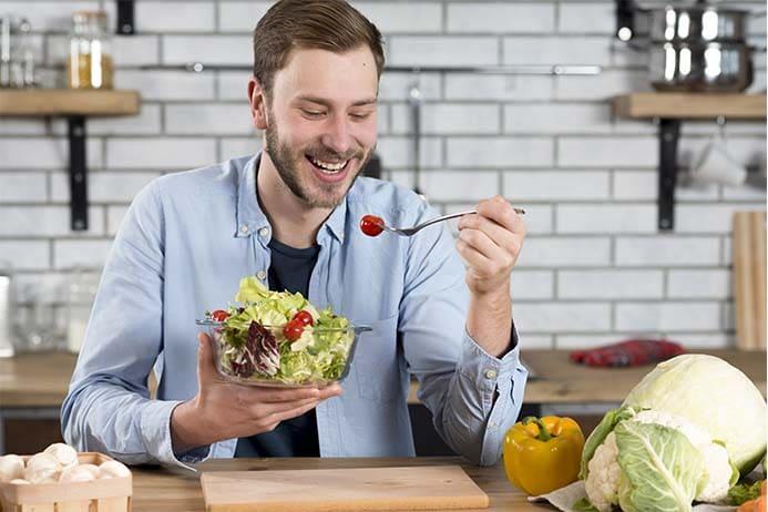 homem feliz e comendo um prato de salada na cozinha de casa