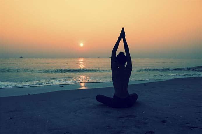 garota fazendo posição de yoga e meditando em frente ao mar num lindo pôr do sol