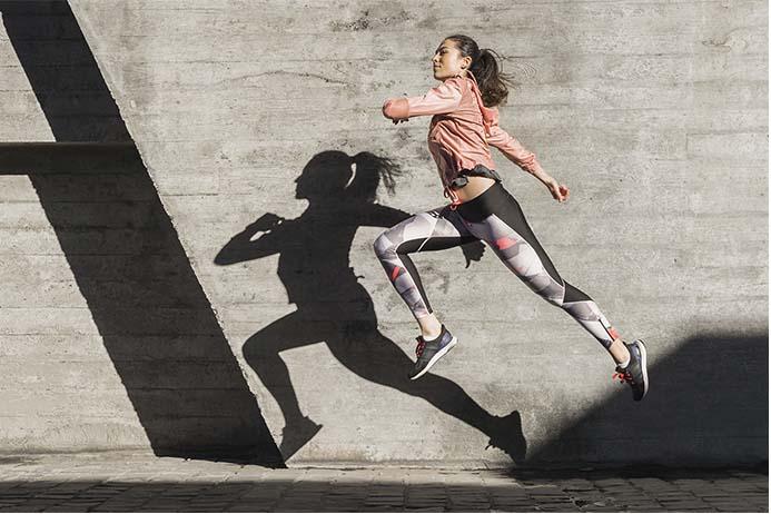 mulher praticando corrida de rua com muita energia