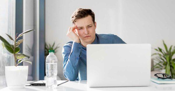 Homem senatdo numa mesa de escritório de frente ao computador com feições de sofrimento